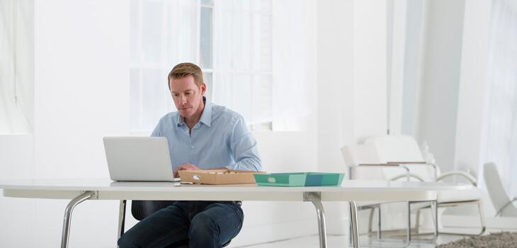 Mann an Notebook informiert sich zu überzeugender Selbstpräsentation