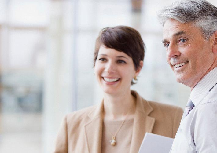Eine junge Frau und ein grauhaariger Mann im Büro – sie hat ihm gezeigt, warum sie die beste Wahl für die offene Stelle ist, geholfen hat ihr das Bewerbungscoaching.