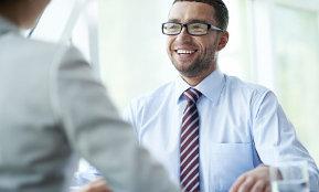 Zwei Männer unterhalten sich im Büro über Bewerbungsberatung