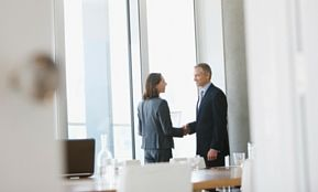 Zwei Menschen geben sich die Hand im Büro – hier geht es um Kündigungsarten, Kündigungsgründe und Personalabbau