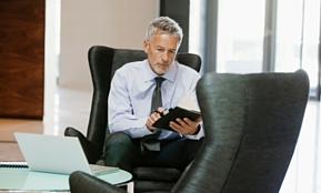 Ein Mann mit Krawatte informiert sich vor dem Personalabbau über Kündigungsfristen in diesem Artikel