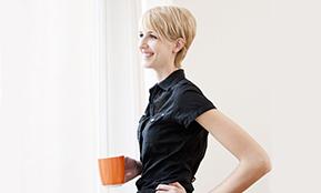 Eine Frau mit einer Tasse ist zuversichtlich - Wie einen neuen Job finden und gleichzeitig die Motivation erhalten? Dazu gibt es hier Tipps.