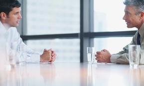 Zwei Mitarbeiter im Gespräch – der Text berichtet über Fallstricke bei Personalfreisetzung, Mitarbeiter- und einer Massenentlassung, die Arbeitgeber kennen sollten