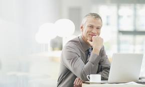 Ein lächelnder Mann im Büro – er weiß, dass sich die Kosten für Personalabbau und Outplacement letztendlich rechnen