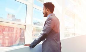 Ein Mann blickt nachdenklich aus einem Bürofenster – hier geht es zum Fachartikel Was ist eine Transfergesellschaft?