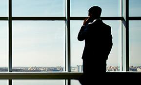 Ein Mann steht nachdenklich am Fenster – die Fotografie illustriert einen Bericht darüber, wann Personalabbau unvermeidlich ist